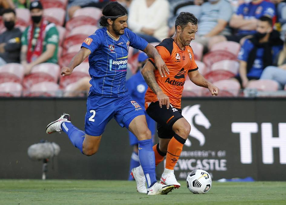 HEAD TO HEAD: Johnny Koutroumbis challenges Roar striker Scott McDonald for possession in the nil-all draw at Dolphin Stadium on Sunday. Picture: AAP