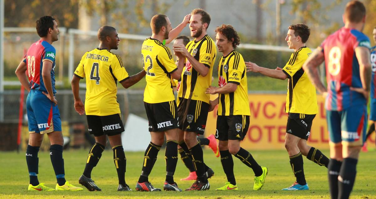 CHANCE: Jeremy Brockie, centre, celebrates a goal for Wellington against Newcastle in a 2014 trial game at Magic Park. Picture: Ryan Osland
