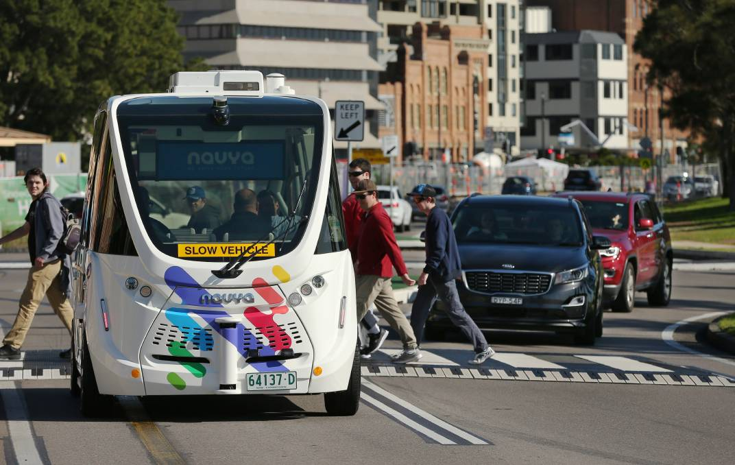 EASY DOES IT: The driverless bus stops for pedestrians in Wharf Road. Pictures: Simone De Peak
