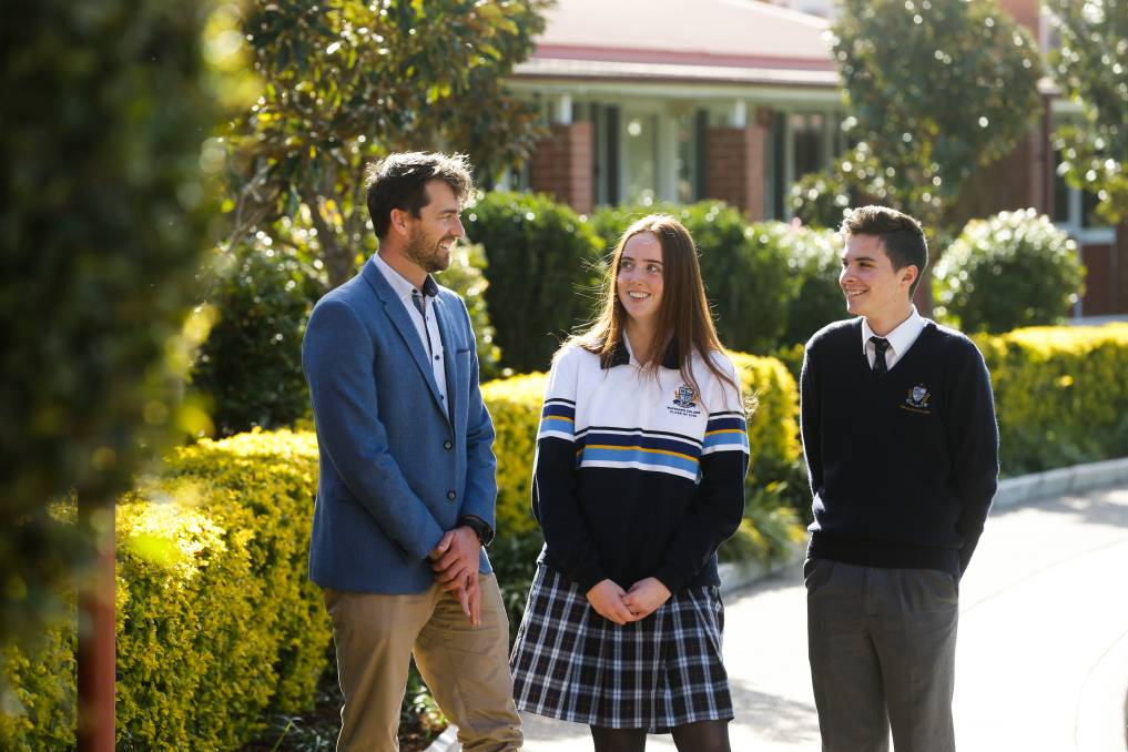 New direction: Macquarie College assistant principal of wellbeing Joshua Brown with students Georgia Scott and Oscar Priest. He will speak at the conference next Monday. Picture: Jonathan Carroll