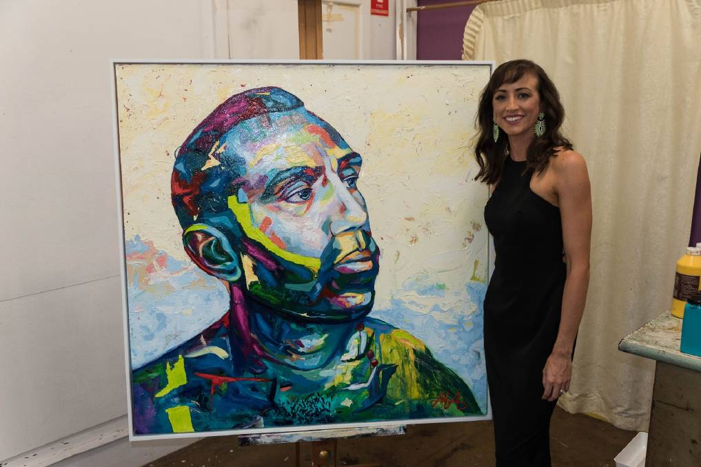ENTRY: Artist Megan Adams with her multicoloured portrait of Adam Goodes, who was subject to ugly racism in the final year of his AFL career. Adams will enter the piece in this year's Archibald Prize.