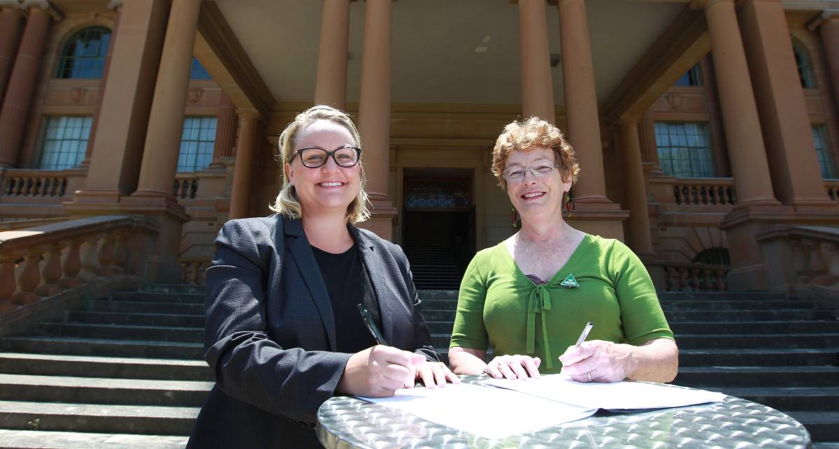 AGREEMENT: Lord mayoral candidates Nuatali Nelmes and Therese Doyle signing the 'open government reform package' as part of a preference deal between Labor and the Greens in the lead up to the 2014 by-election.