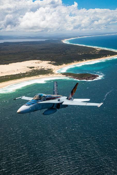 FAREWELL: Royal Australian Air Force F/A-18A Hornet A21-23 aircraft with Worimi livery flying over Port Stephens. Picture: AC Adam Abela