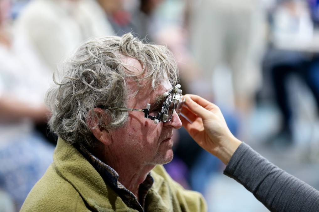 SERVICE: Robert Rigby gets his eyes tested by OPSM Maitland's Roslyn Go. Picture: Jonathan Carroll