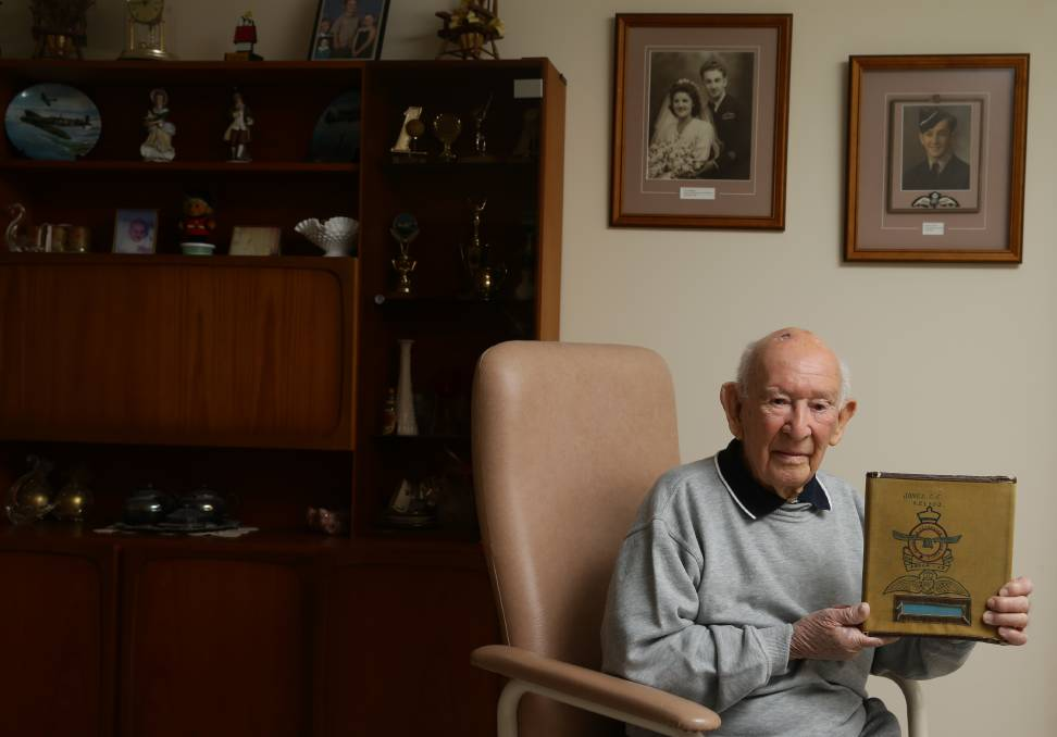 World War Two Spitfire pilot Clem Jones, with his flying log book, which he decorated with a drawing of the Royal Australian Air Force insignia. Picture: Jonathan Carroll